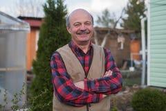 Bejaarde in vest op de achtergrond van het huis in het dorp royalty-vrije stock foto's