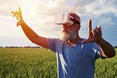 Bejaarde in virtuele werkelijkheid Stock Afbeeldingen