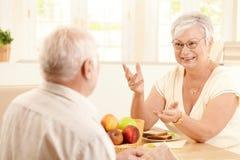 Bejaarde vrouw die aan echtgenoot bij ontbijt babbelt Stock Afbeeldingen