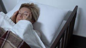 Bejaarde vrouwelijke patiënt die tempels masseren, die aan vreselijke migraine in ziekbed lijden stock video