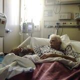Bejaarde, witte haired mannelijke patiënt in het ziekenhuisbed stock afbeeldingen