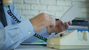 Bejaarde zakenman in bureauruimte die oude telefoon met behulp van die een telefoonaantal draaien stock footage