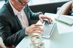 Bejaarde zakenman die laptop in koffie met behulp van royalty-vrije stock fotografie