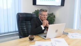 Bejaarde zakenman die met computer in modern bureau werken stock afbeeldingen