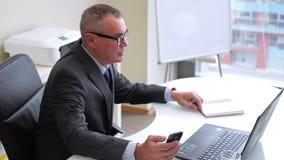 Bejaarde zakenman die met computer in modern bureau werken stock videobeelden