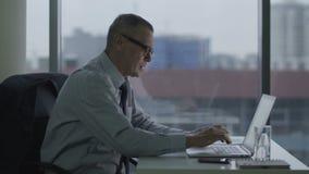 Bejaarde zakenman die met computer in modern bureau werken zijn rug is kwetst stock videobeelden