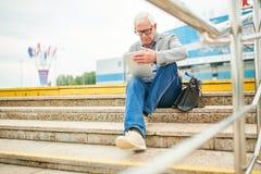 Bejaarde zakenman die tablet op stappen gebruiken stock fotografie