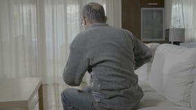 Bejaarde zieke mens met reumatiek die en zijn rug uitrekken masseren die een pijnlijke klem hebben - stock videobeelden
