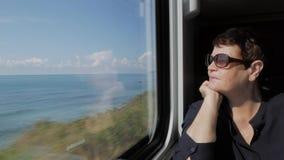 Bejaarde in zonnebril dichtbij venster aan de gang stock footage