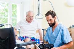 Bejaarde zorgverpleegster die oudste van bed helpen om stoel te rijden royalty-vrije stock foto