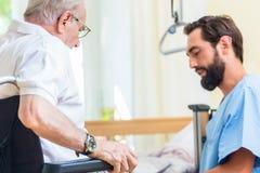Bejaarde zorgverpleegster die oudste van bed helpen om stoel te rijden royalty-vrije stock fotografie