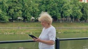 Bejaardegangen langs de waterkant en het gebruiken van tabletcomputer met oortelefoons stock footage