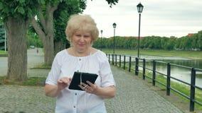 Bejaardegangen langs de waterkant en het gebruiken van tabletcomputer met oortelefoons Rivier op de achtergrond stock videobeelden