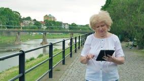 Bejaardegangen langs de waterkant en het gebruiken van tabletcomputer met oortelefoons Rivier op de achtergrond stock footage