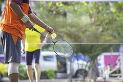 Bejaardehand die een van de achtergrond badmintonracket onduidelijk beeldboom in park houden royalty-vrije stock fotografie