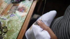 Bejaardehanden die Dwarssteek op Wit Katoenen Canvas doen 4K, sluit omhoog, Langzame Motie stock footage