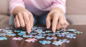 Bejaardehanden die puzzelclose-up doen stock afbeeldingen