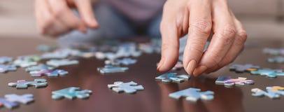 Bejaardehanden die puzzelclose-up doen stock fotografie