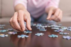 Bejaardehanden die puzzelclose-up doen stock afbeelding