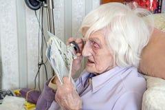 Bejaardelezing met gezichtsstoornissen met het overdrijven loupe stock afbeeldingen
