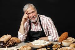 Bejaarden die de professionele chef-kokmens glimlachen Ge?soleerdn over zwarte achtergrond royalty-vrije stock afbeeldingen