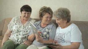 Bejaarden die digitale tabletten thuis houden stock footage