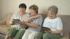 Bejaarden die foto's die digitale tabletten gebruiken kijken stock video