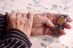 Bejaarden die haar horloge houden Royalty-vrije Stock Foto