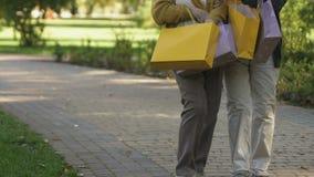 Bejaarden die samen met het winkelen zakken in park, vrouwelijke vriendschap lopen stock video
