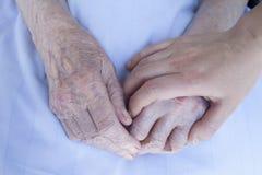 Bejaarden en jonge vrouwenhanden Stock Foto's