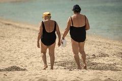 Bejaardengangen bij kust, overzees op achtergrond Dames die in zwempakken bij zandstrand lopen, achtermening Oude oma's Royalty-vrije Stock Afbeelding