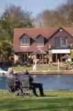 Bejaardepaar het ontspannen op bank die van pensionering genieten Stock Afbeeldingen