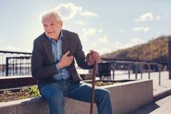 Bejaardewinst die ziek wegens borstpijn voelen royalty-vrije stock foto