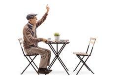 Bejaardezitting bij een koffietafel en het roepen van een kelner royalty-vrije stock foto's