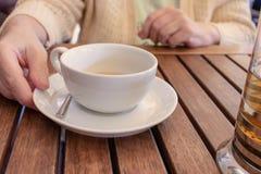 Bejaardezitting door de lijst en holding een kop thee royalty-vrije stock afbeelding