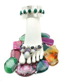 Bejeweled Foot. Foot display form with anklet and toe jewelry, surrounded by many colorful gemstone talismans Stock Images
