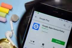 Google Apps Device Policy dev app with magnifying on Smartphone screen stock images