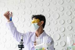 Beker en kleurrijke vloeistof stock foto's