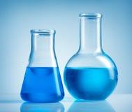 Bekers en blauwe vloeistof Stock Foto