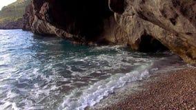 Bekiezeld strand bij een rotsachtige kust stock videobeelden