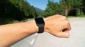 Bekijkend smartwatch of sporthorloge, controlerend gps de kaart van de navigatiepositie of de impulsspoor van het harttarief Spor royalty-vrije stock afbeeldingen