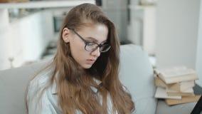Bekijkt de tiener gelezen tekst op laptop, het scherm, schrijft iets in notitieboekje, die voor examens voorbereidingen treffen stock footage