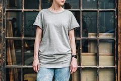 Bekläda beskådar Är den iklädda gråa t-skjortan för den unga millennial kvinnan ställningar mot fönster Fotografering för Bildbyråer