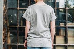 Bekläda beskådar Är den iklädda gråa t-skjortan för den unga millennial kvinnan ställningar mot fönster Arkivfoto