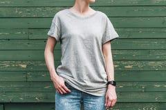 Bekläda beskådar Är den iklädda gråa t-skjortan för den unga millennial kvinnan ställningar mot den gröna wood väggen Royaltyfri Bild