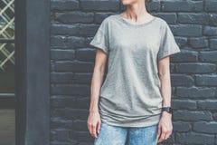 Bekläda beskådar Är den iklädda gråa t-skjortan för den unga millennial kvinnan ställningar mot den mörka tegelstenväggen Arkivfoto