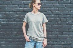Bekläda beskådar Är den iklädda gråa t-skjortan för den unga millennial kvinnan ställningar mot den mörka tegelstenväggen Royaltyfri Foto