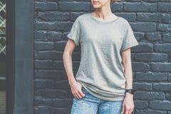 Bekläda beskådar Är den iklädda gråa t-skjortan för den unga millennial kvinnan ställningar mot den mörka tegelstenväggen Royaltyfria Foton