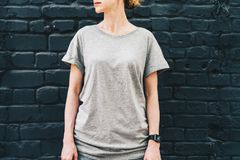 Bekläda beskådar Är den iklädda gråa t-skjortan för den unga millennial kvinnan ställningar mot den mörka tegelstenväggen Royaltyfria Bilder