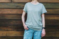 Bekläda beskådar Är den iklädda gråa t-skjortan för den unga millennial kvinnan ställningar mot den mörka wood väggen Royaltyfria Bilder